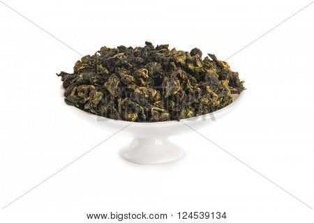 Tie Guan Yin Oolong tea on white porcelain container, isolated on white background