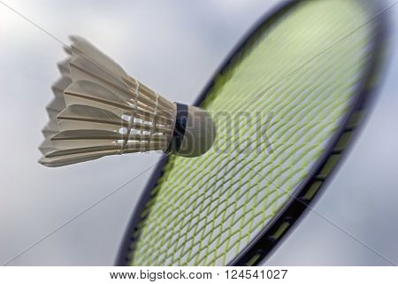 Badminton racket striking shuttlecock closeup and high up