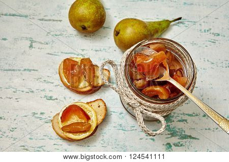 Pear jam in a glass on a wooden table. Sandwiches with pear jam and pickled lemons. Healthy breakfast