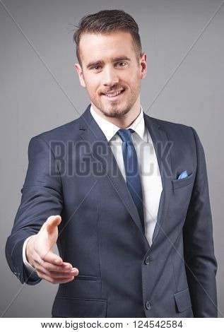 Successful young businessman giving his hand for handshake