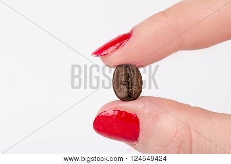 Hand holding a coffee bean between fingers. Coffee beans and hand on a white background. Isolated.