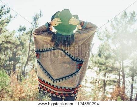 Young woman wearing in poncho and hat walking in the forest rear view