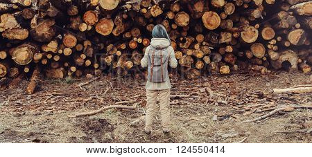 Unrecognizable young woman with backpack standing on background of stack felled tree trunks rear view