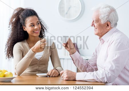 Young happy caregiver and senior smiling man drinking cup of coffee together at home