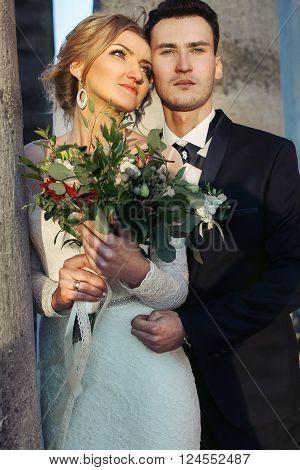 Romantic Elegant Newlywed Couple Hugging Near Columns At Sunset Closeup