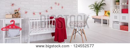 Modern designed white cozy corner with cradle for little baby. On the night stand teddy bear and baby's clothes