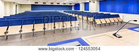 Modern decor of seminar hall on medical university. Blue chairs in spacious classroom