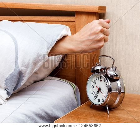 Woman stopping the alarm clock in the bedroom