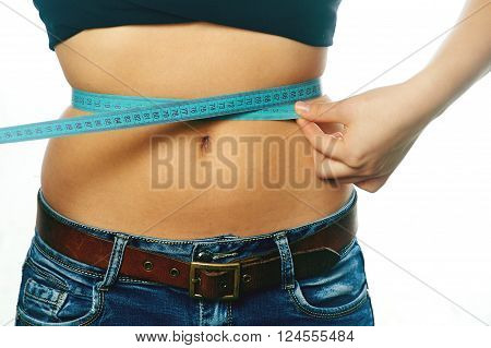 Young girl measuring waist with a white background