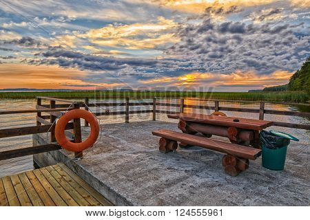 Warm Romantic Sunset Lake Pier with Camping Table and Bench