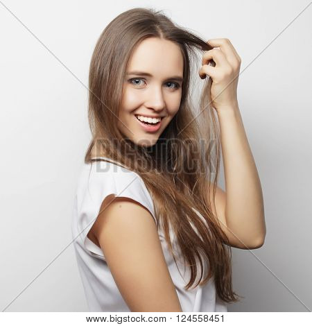 Young beautiful woman posing with  white t-shirts, ower white background
