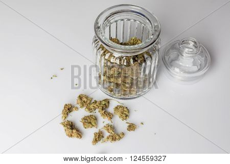 Medical cannabis buds in an open glass jar with marijuana flowers scattered aside and transparent lid on white background from high angle