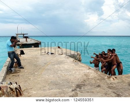 Andaman-Apr 14: A photographer taking picture of Andamanese children at a jetty Apr 14, 2012 in Andaman and Nicobar Islands, India, Asia.