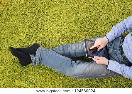 young man sitting on a green carpet with tablet