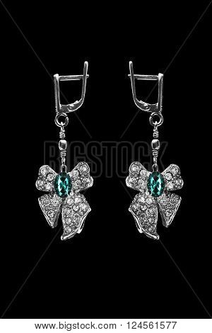 Topaz and crystals earrings in the shape of a bow isolated over black