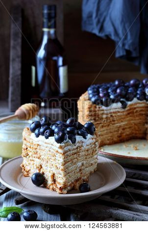 piece of honey cake decorated with blueberry on a background of cognac bottles jars of honey and cake
