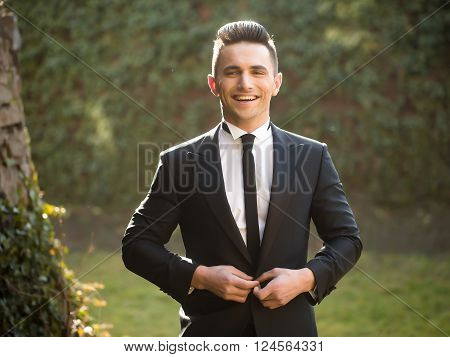 Young Man Buttons Suit Coat