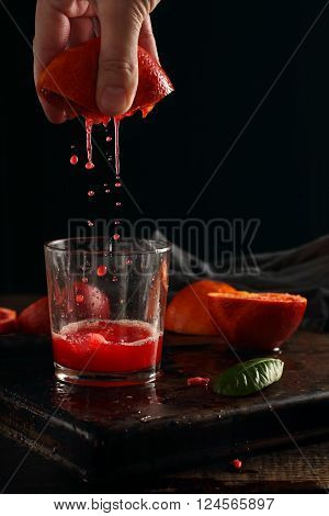 Squeezing juice from blood oranges photographed with flash on a black background