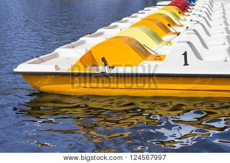line of pedal boats on a pier - row of boats