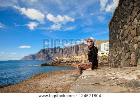 Young caucasian beautiful woman on seascape on tropical island Tenerife Canary in Spain. Los Gigantes landscape on ocean.