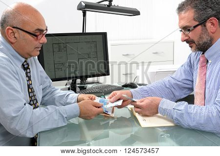 Businessmen engaged in a financial transaction with banknotes of the Euro