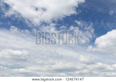 Huge curly patterned white clouds in the blue sky during the day without the sun