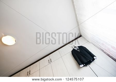 Black suit with shirt hanging from a wooden cupboard
