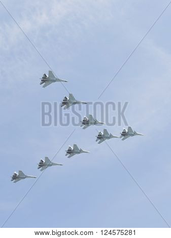 Moscow-May 9 2015: Eight powerful multipurpose heavy fighter gray-blue Su-30 flying high in the blue sky at the Victory Day parade May 9 2015 Moscow Russia