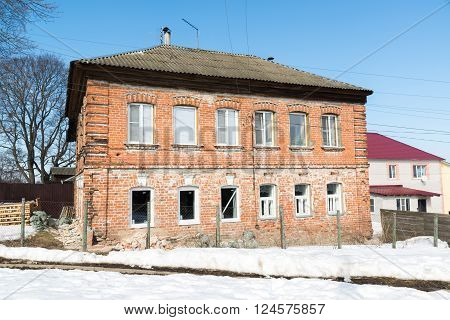 Old brick two-storey house with a new plastic windows