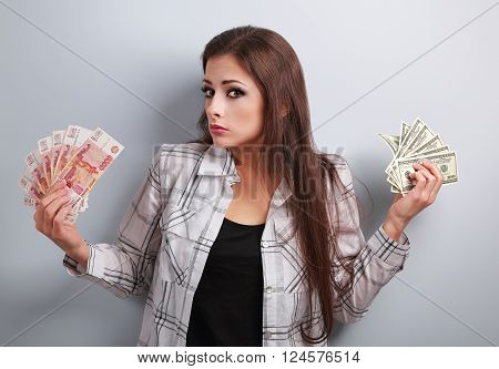 Serious unhappy business woman thinking that currency to choose, dollars or rubles, holding money in different hands