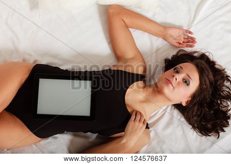 Sexy lazy girl in body underwear lying with tablet touchpad blank copy space on bed. Woman relaxing lazing in bedroom. Internet.
