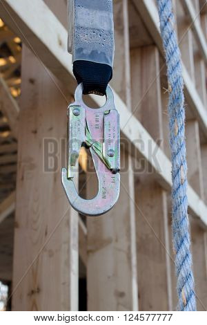 hook is hanging on safety rope and wooden lathing on background