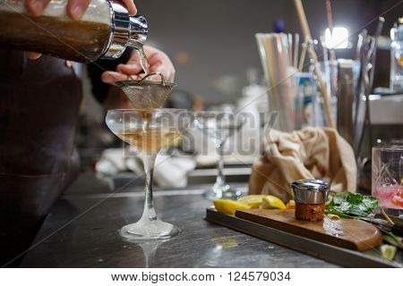 Bartender coocks cocktail behind a bar counter