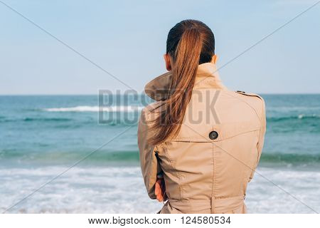 Brunette in beige coat looks on the sea the view from the back