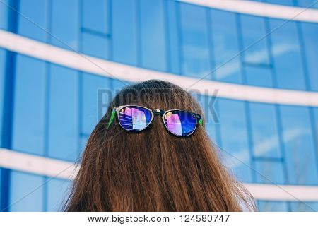 Colored Sun Glasses At The Nape Of The Girl On A Blue Background