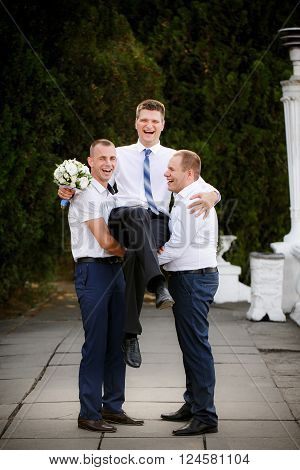 Groomsmen hold the groom at the hands ** Note: Soft Focus at 100%, best at smaller sizes