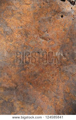 Close up of a rusted metal sheet with orange and brown colours