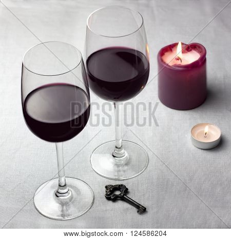 Two glasses of wine on a grey tablecloth with an old key and two candles with copyspace