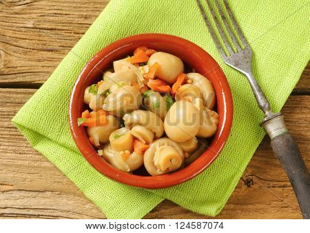 bowl of picked champignons on green place mat