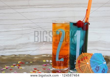 Two glasses with the numbers 2 & 1 printed on them filled with bright cocktails