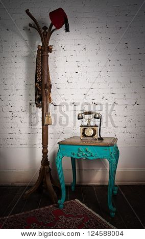 Retro composition of old telephone set on green wooden vintage table and red fez and scarf hanged on an old wooden coat hanger on a background of red carpet dark brown wooden floor and white bricks wall