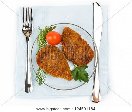 Chicken cutlet on a blue napkin. Serving with a knife and fork.