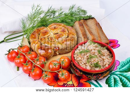 Barley porridge and ring bratwurst. Decorated with cherry tomatoes and herbs.