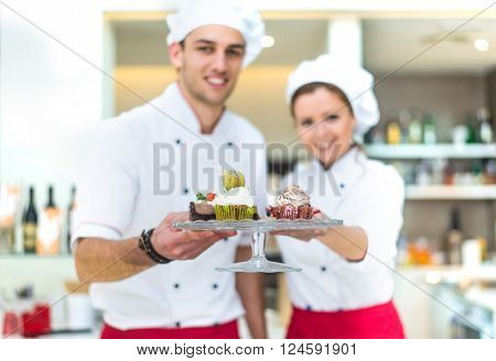Two pastry chefs preparing desserts in a pastry shop