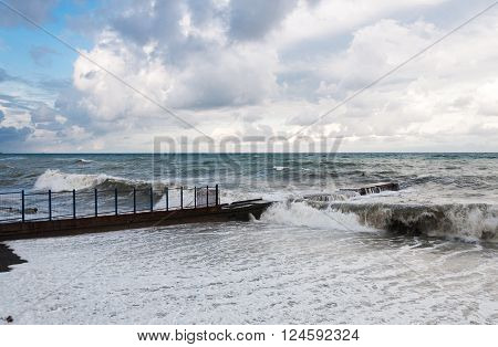 Storm waves roll on the concrete breakwater.