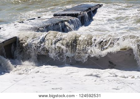 Storm waves roll on the concrete breakwater. ** Note: Visible grain at 100%, best at smaller sizes