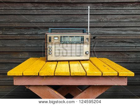 Old radio on yellow table in the garden