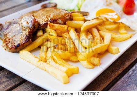 French fries and fried meat fried egg.