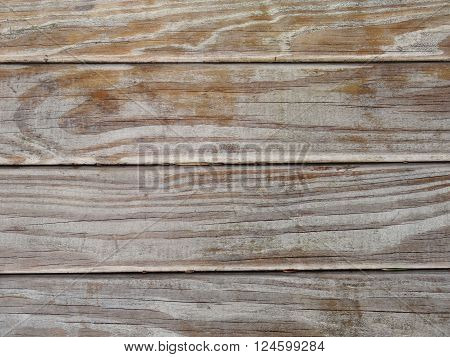 Macro of strongly weathered wood. Naturally aged by the elements. Horizontal cracks can be seen in the well dried wood. The color is partially worn away and shows the grain of the wood. The macro shows four horizontal planks.