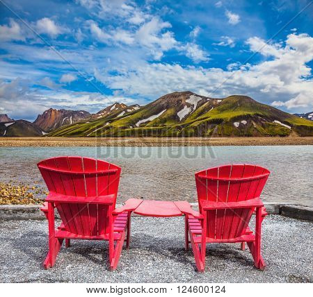 Two comfortable red deck chairs are for rest.  Valley among the rhyolite mountains and shallow streams